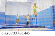 Купить «View through yellow safety net of young sporty people exercising jump elements in trampoline center», видеоролик № 33480445, снято 2 июля 2020 г. (c) Яков Филимонов / Фотобанк Лори
