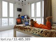 Семья дома, ребенок лежит на кровати и учится в ноутбуке, мама на дальнем плане работает удаленно в компьютере. Стоковое фото, фотограф Иванов Алексей / Фотобанк Лори