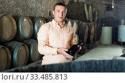 Купить «Customer holding bottle of wine», фото № 33485813, снято 22 сентября 2016 г. (c) Яков Филимонов / Фотобанк Лори