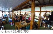 tourists on the lower deck of a sea vessel floating near the rocky shores (2019 год). Редакционное видео, видеограф Aleksandr Sulimov / Фотобанк Лори