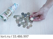 Female hand with a ruble. Glass jar with Russian bills and coins on the table. The concept of savings. Стоковое фото, фотограф Катерина Белякина / Фотобанк Лори