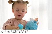 Girl feeding baby doll at home. Стоковое видео, видеограф Ekaterina Demidova / Фотобанк Лори