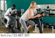 Купить «Couple training on exercise bikes», фото № 33487301, снято 25 февраля 2019 г. (c) Яков Филимонов / Фотобанк Лори