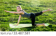 Купить «girl exercising on mat in morning outdoor», фото № 33487581, снято 8 июня 2017 г. (c) Яков Филимонов / Фотобанк Лори