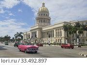 Купить «Classic cars drive past the Capitolio building, Havana, Cuba.», фото № 33492897, снято 6 марта 2020 г. (c) age Fotostock / Фотобанк Лори