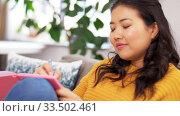 Купить «asian woman with diary sitting on sofa at home», видеоролик № 33502461, снято 30 марта 2020 г. (c) Syda Productions / Фотобанк Лори