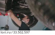 Купить «Auto repair shop - young man working under the car with a wrench», видеоролик № 33502597, снято 8 апреля 2020 г. (c) Константин Шишкин / Фотобанк Лори