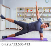 Купить «Young man exercising at home in sports and healthy lifestyle con», фото № 33506413, снято 3 мая 2017 г. (c) Elnur / Фотобанк Лори