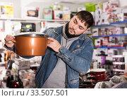 Купить «Attentive buyer inspects new pot in a hardware store», фото № 33507501, снято 28 января 2020 г. (c) Яков Филимонов / Фотобанк Лори