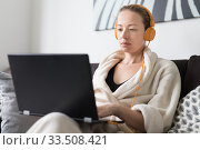Stay at home and social distancing. Woman in her casual home bathrobe working remotly from her living room. Video chatting using social media with friend, family, business clients or partners. Стоковое фото, фотограф Matej Kastelic / Фотобанк Лори