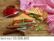 Купить «Sandwich with tomatoes, cheese and ham on a dark, wooden background», фото № 33508805, снято 8 апреля 2020 г. (c) Марина Володько / Фотобанк Лори