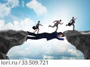 Купить «Businessman acting as a bridge in support concept», фото № 33509721, снято 27 мая 2020 г. (c) Elnur / Фотобанк Лори