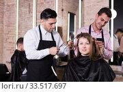 Brunette getting haircutting from two hairstylists. Стоковое фото, фотограф Яков Филимонов / Фотобанк Лори