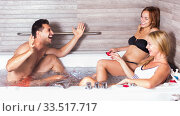Купить «Three friends are resting in jacuzzi with petals», фото № 33517717, снято 18 июля 2017 г. (c) Яков Филимонов / Фотобанк Лори