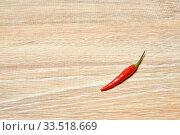 Single pod of red chili pepper lies on a wooden surface. Стоковое фото, фотограф Евгений Харитонов / Фотобанк Лори