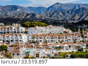 Apartment houses in front of mountain scenery in the resort of Nerja, Andalusia, Spain, Europe. Редакционное фото, агентство Caro Photoagency / Фотобанк Лори