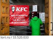 """Купить «Курьер """"Delivery Club"""" стоит у пункта выдачи заказов сети ресторанов общественного питания KFC в городе Москве во время эпидемии коронавируса COVID-19 в России. Логотип компании KFC был изменен и добавлена маска на лицо.», фото № 33520033, снято 9 апреля 2020 г. (c) Николай Винокуров / Фотобанк Лори"""