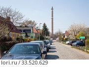 Detached houses and chimney from the Marzahn combined heat and power plant in Kroever Strasse in Berlin-Marzahn (2019 год). Редакционное фото, агентство Caro Photoagency / Фотобанк Лори