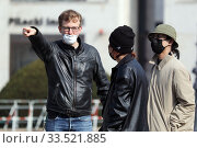 Berlin, Germany, man with mouth guard shows Asian tourists the way. Редакционное фото, агентство Caro Photoagency / Фотобанк Лори