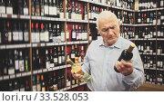 Купить «Serious elderly man chooses between red and white wine in a liquor store», видеоролик № 33528053, снято 25 мая 2020 г. (c) Яков Филимонов / Фотобанк Лори
