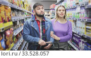 Portrait of young loving couple walking among shelves with groceries in supermarket. Стоковое видео, видеограф Яков Филимонов / Фотобанк Лори