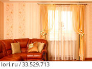 Brown leather sofa with beautiful pillows, a row a window with a curtain. Horizontal shot shot. The embroidery isn't a handiwork, this repetition of drawing on wall-paper. Стоковое фото, фотограф Zoonar.com/Sergey Chirkov / age Fotostock / Фотобанк Лори