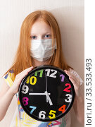 Купить «Adorable red haired girl wearing medicine mask for stop coronavirus outbreak and girl holds a clock. Self isolation at home.  Concept. Time goes by. Vertical photo», фото № 33533493, снято 10 апреля 2020 г. (c) Evgenia Shevardina / Фотобанк Лори