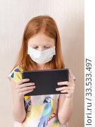 Купить «Adorable red haired girl wearing medicine mask for stop coronavirus outbreak. 8 years old girl look at tablet. Self isolation at home. Education from home. Vertical photo», фото № 33533497, снято 10 апреля 2020 г. (c) Evgenia Shevardina / Фотобанк Лори