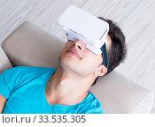 Купить «Young man wearing VR glasses relaxing on couch sofa», фото № 33535305, снято 10 августа 2017 г. (c) Elnur / Фотобанк Лори