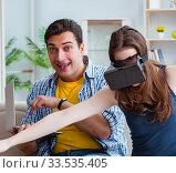 Купить «Young family playing games with virtual reality glasses», фото № 33535405, снято 23 мая 2017 г. (c) Elnur / Фотобанк Лори