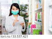 Купить «Chinese woman pharmacist in protective facial mask keeps track of drugs in interior of pharmacy», фото № 33537421, снято 26 февраля 2020 г. (c) Яков Филимонов / Фотобанк Лори