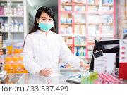 Купить «Young chinese druggist in protective facial mask», фото № 33537429, снято 26 февраля 2020 г. (c) Яков Филимонов / Фотобанк Лори