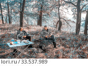 Two men sit at a table on a halt in the autumn forest near the fireplace. Стоковое фото, фотограф Акиньшин Владимир / Фотобанк Лори