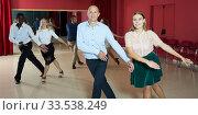 Active smiling people practicing lindy hop movements in dance class. Стоковое фото, фотограф Яков Филимонов / Фотобанк Лори