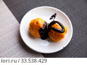 Sweet baked profiteroles with hot chocolate cream at plate. Стоковое фото, фотограф Яков Филимонов / Фотобанк Лори
