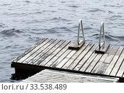 Купить «Old wooden pier with metal rails for swimming», фото № 33538489, снято 26 октября 2019 г. (c) EugeneSergeev / Фотобанк Лори