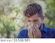 Cells of Covid-19 coronavirus spreading and infecting over sick man blowing his nose. Стоковое фото, агентство Wavebreak Media / Фотобанк Лори