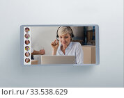 Caucasian woman wearing headphone set during a visio call on digital tablet. Стоковое фото, агентство Wavebreak Media / Фотобанк Лори