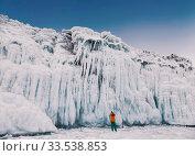 Fabulous ice icicles on the rocks of lake Baikal. Tourist photographs the icy rocks. Eastern Siberia, Russia. Стоковое фото, фотограф Наталья Волкова / Фотобанк Лори