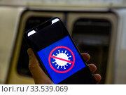 """Логотип приложения """"Госуслуги Стоп Коронавирус"""" с Google Play на телефоне для получения электронных пропусков в режиме самоизоляции на фоне входа в вагон метро (2020 год). Редакционное фото, фотограф Николай Винокуров / Фотобанк Лори"""
