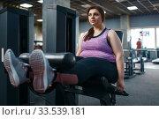 Купить «Overweight woman pumps press, exercise in gym», фото № 33539181, снято 28 декабря 2019 г. (c) Tryapitsyn Sergiy / Фотобанк Лори