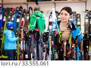 Attractive girl choosing ski poles for skiing in store of sports equipment. Стоковое фото, фотограф Яков Филимонов / Фотобанк Лори