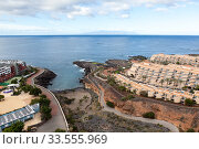 Empty coastline of the Playa Paraiso village with hotel buildings. The La Gomera island is on horizon. Tenerife, Canary islands. Spain (2016 год). Стоковое фото, фотограф Кекяляйнен Андрей / Фотобанк Лори
