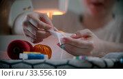 Купить «Young woman designer putting pins in the white cloth», видеоролик № 33556109, снято 5 июня 2020 г. (c) Константин Шишкин / Фотобанк Лори