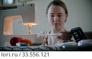 Купить «Young woman designer sewing a mask using a sewing machine», видеоролик № 33556121, снято 4 июля 2020 г. (c) Константин Шишкин / Фотобанк Лори