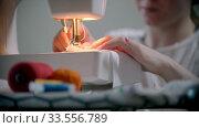 Купить «Young woman designer sewing a reusable mask using a sewing machine», видеоролик № 33556789, снято 4 июля 2020 г. (c) Константин Шишкин / Фотобанк Лори