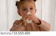 Купить «Child drinks milk from a bottle», видеоролик № 33559405, снято 8 апреля 2020 г. (c) Ekaterina Demidova / Фотобанк Лори