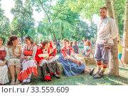 Купить «Russia Samara August 2019: Flower Festival. Girls in national Russian costumes are sitting on straw bundles.», фото № 33559609, снято 24 августа 2019 г. (c) Акиньшин Владимир / Фотобанк Лори
