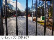 Купить «Центральный парк закрыт для посетителей из-за эпидемии коронавируса, г. Королев, Россия. Вид на парк сквозь закрытую решетку ворот.», фото № 33559937, снято 15 апреля 2020 г. (c) chaoss / Фотобанк Лори