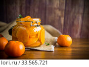 Купить «tangerine jam in a glass jar on a wooden table», фото № 33565721, снято 16 апреля 2020 г. (c) Peredniankina / Фотобанк Лори
